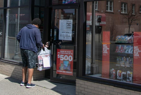 Leondre Leonard, 33, of Warren is greeted by a GameStop employee in Hamtramck to pick up a PS4 PlayStation he ordered online. Leonard, who said he was really bored, mentioned this was the only time he has gone out. GameStop is open in spite of a stay at home mandate due to the spread of the Novel Corona Virus.