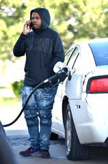 D.A. Price of Detroit fills up for a Warren Marathon station on Wednesday. Regular gas was 99 cents as prices have fallen due to reduced demand.