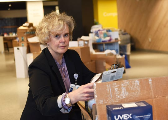 Melanie Fisher, senior vice president for Beaumont, with a donated box of N95 face masks in the lobby of the corporate headquarters.