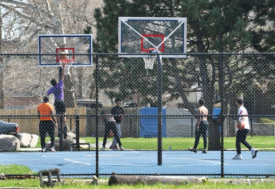 Some young men shoot around on a basketball court at Delores Bennett Park in Detroit on April 8, 2020.