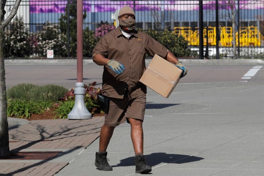 A UPS driver wears a mask as he makes a delivery, Monday, April 6, 2020, in Renton, Wash.