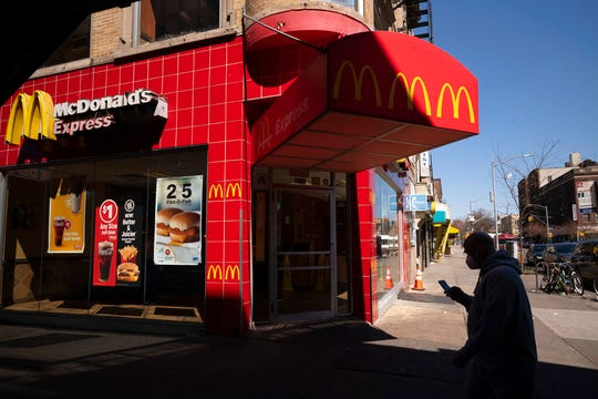 A customer wearing a mask passes a McDonald's restaurant that is open for takeout service during the coronavirus pandemic, Monday, April 6, 2020, in the Brooklyn borough of New York.