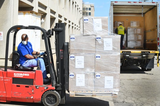 Henry Ford Health System's Cory Jones helps unload over 100,000 KN95 masks from the DTE Foundation to Henry Ford Health System, to be distributed to hospitals across southeast Michigan, in Detroit on April 8, 2020.