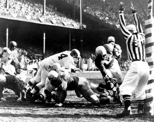 Lions quarterback Tobin Rote runs into the end zone for a touchdown in the 1957 championship game.