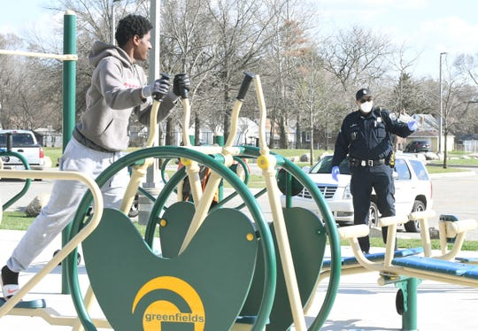 Detroit Neighborhood police officer Dan Robinson checks on a group of 3 working out on fitness equipment at Farwell Field in Detroit.