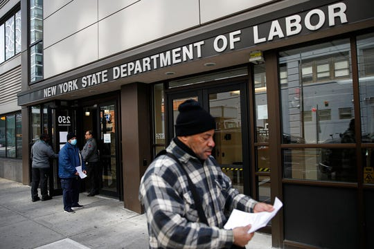Visitors to the Department of Labor are turned away at the door by personnel due to closures over coronavirus concerns in this March 18, 2020, file photo in New York.