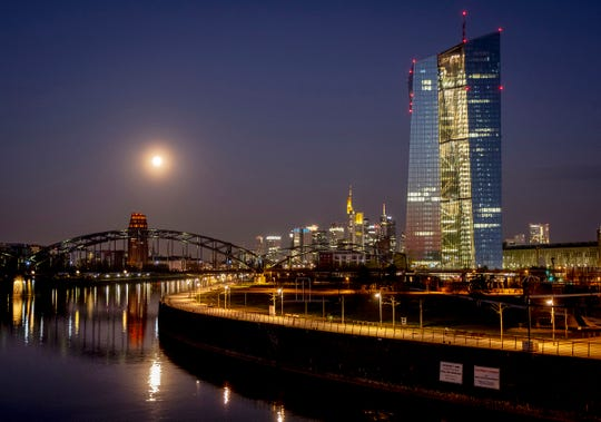 A nearly full moon sets over the buildings of the banking district and the European Central Bank, right, in Frankfurt, Germany, early Tuesday, April 7, 2020.