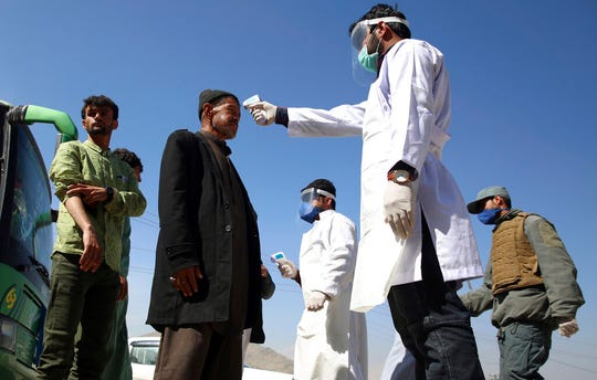 In this Sunday, March 22, 2020 file photo, health workers measure the temperature of Afghan passengers in an effort to prevent the spread of the coronavirus, as they enter Kabul trough Kabul's western entrance gate.