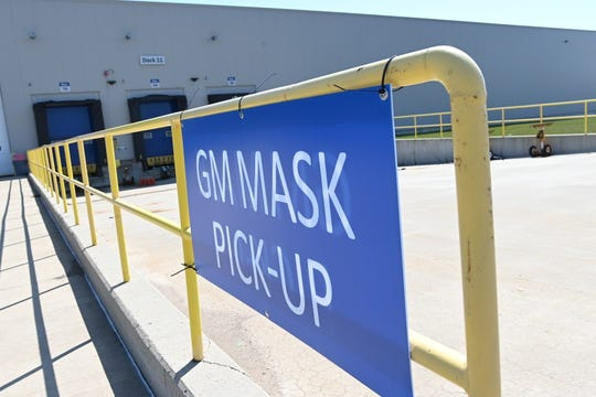 A sign at  GM's formerly idled Warren Transmission plant signals the pickup area for face masks for hospitals.