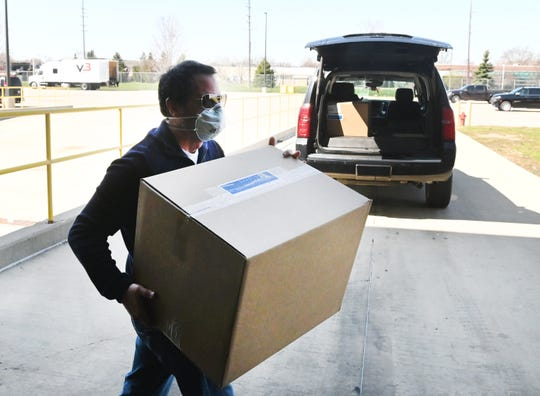 Tony Cervone, GM senior vice-president of global communications,  picks up two boxes filled with 2,800 Level 1 face masks made at the GM Transmission Plant in Warren on Tuesday, April 8, 2020.
