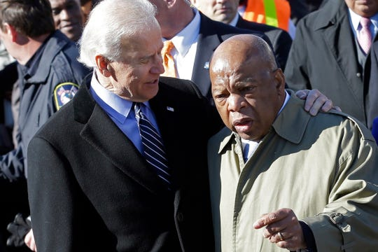 FILE - In this March 3, 2013, file photo, Vice President Joe Biden, left, embraces U.S. Rep. John Lewis, D-Ga., as they prepare to lead a group across the Edmund Pettus Bridge in Selma, Ala.