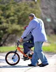 Michael Johnson teaches his foster son how to ride his bike, Wednesday, April 8, 2020.