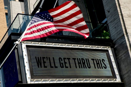 """In this April 6, 2020 photo, a sign at The Anthem music venue reads """"We'll Get Thru This"""" at the wharf which is almost completely empty because of the coronavirus outbreak in Washington."""