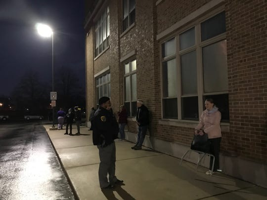 Tom Midthun, center, leans against Green Bay East High School on Tuesday night. He was the last voter to get in line before the polls closed and had an hours-long wait in front of him before he could cast a ballot.