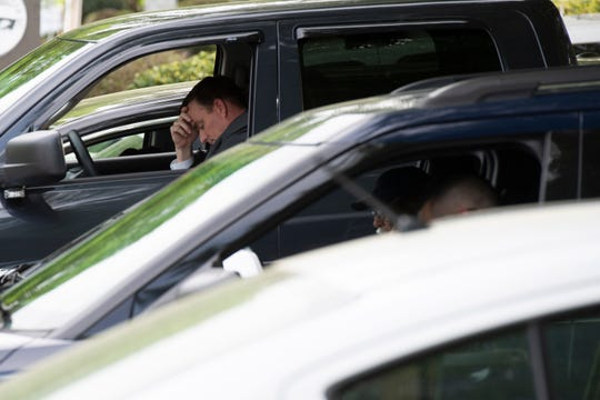 Greenville County sheriff Hobart Lewis bows his head while parked alongside other cars in the parking lot at the Law Enforcement Center Wednesday, April 8, 2020.