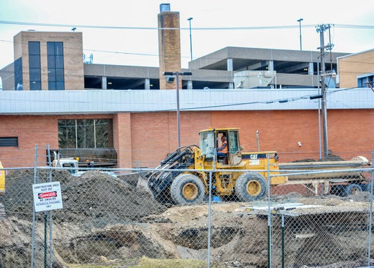 A work crew from Shumaker Trucking and Excavating removes contaminated soil from the parking lot of the Easterseals-Goodwill Personal Car building in downtown Great Falls.
