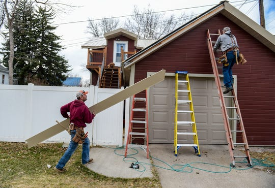 Mark, left, and Scott Munroe, of Munroe Enterprise Inc., install gable flashing on an eave on Tuesday, April 7, 2020.  Mark Munroe, a general contractor, says that some of his larger contracts have been put on hold recently but there are small jobs around Great Falls that keep him busy.