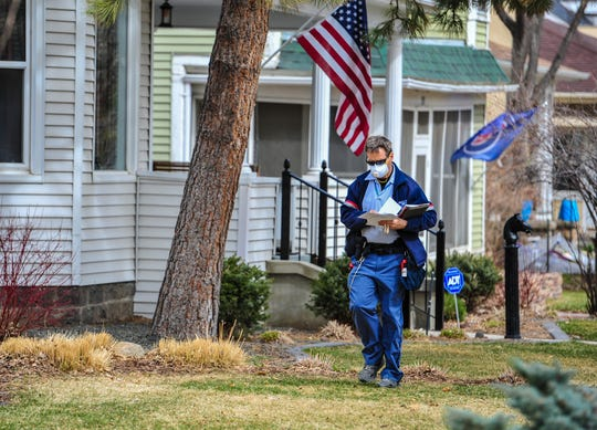 A U.S. Postal Service mail carrier delivers mail near downtown Great falls Tuesday. Paper census questionnaires were mailed to about 64 million households across the nation Wednesday. Residents can also respond at 2020census.gov.