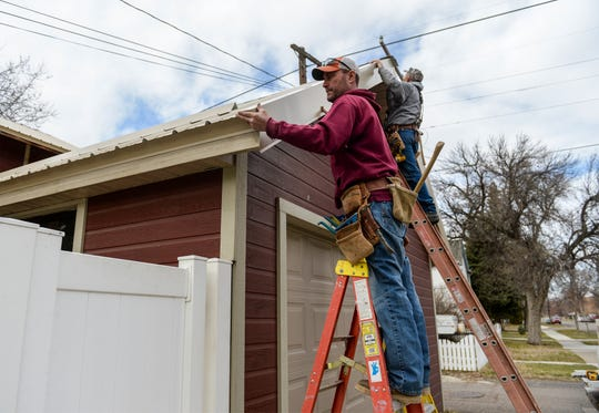 Mark, left, and Scott Munroe of Munroe Enterprise Inc. install gable flashing on an eave on Tuesday, April 7, 2020.  Mark Munroe, a general contractor, says that some of his larger contracts have been put on hold recently but there are small jobs around Great Falls that keep him busy.