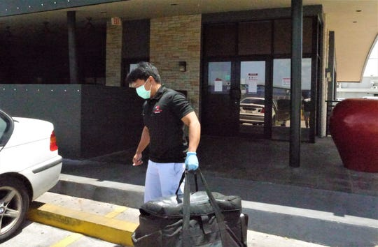 Good to Go driver Darwin Peralta, loads up lunch at Applebee's Bar and Grill April 8. Hungry residents have turned to social media, the internet and apps to find their meals.