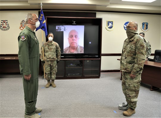 From left, Col. Christopher Faurot, incoming commander;,Chief Master Sgt. Luis Camacho, guidon bearer; Col. D. Graham Botha, outgoing commander, via FaceTime; and Brig. Gen. Johnny S. Lizama, assistant adjutant general,  Guam Air National Guard, at Friday's change of command ceremony.
