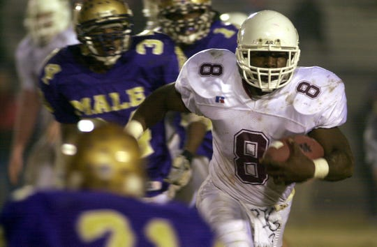 Alex Fendrick (8) runs the ball through Male defenders during their semifinal state game at Louisville Friday night, November 29, 2002.