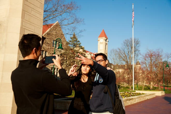 March 23, 2020 - Bloomington, Indiana: Aman Kant, an international student from New Delhi, poses for photos with his girlfriend at Indiana University's iconic Sample Gates. With classes transitioning online for the semester and travel restrictions in place, many international students were grappling with whether or how to go home.