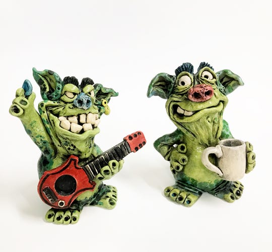 A dragon created by Sam Clark stands ready to play the guitar while another keeps company.