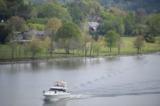 A boat travels down the Tennessee River as trees bloom in Cherokee Park in Knoxville on April 8, 2020.