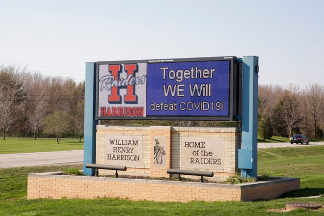 "A sign outside Harrison High School reads ""together we will defeat Covid-19,"" Tuesday, April 7, 2020 in West Lafayette."