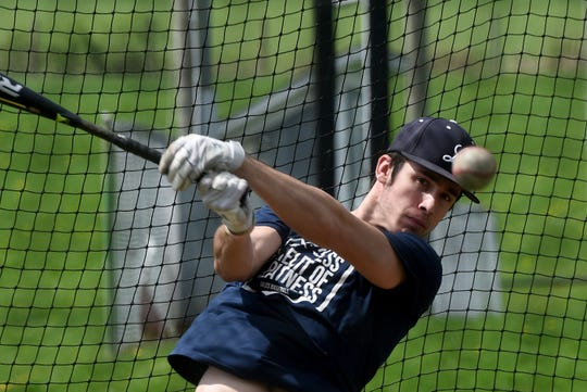 Lancaster High School senior baseball player Casey Finck practices hitting in one of the batting cages by the team's practice field on Wednesday, April 8, 2020.