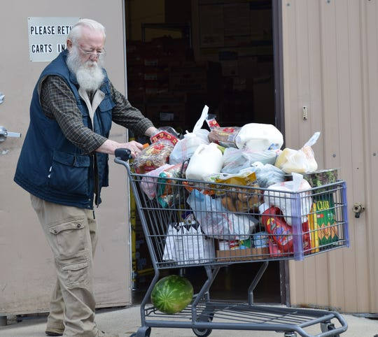 Ernie Conant, a volunteer with Lutheran Social Services Fairfield County Food Pantry, pushes a cart to a customer's car Wednesday, April 8. The pantry has changed its format to follow state healthy guidelines.