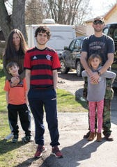 Pedro Vasconcellos, a foreign exchange student from Brazil, stands with his host family, from left, Jenny Myers with her son 5-year-old son River and Mike Myers with daughter Meadow, 7 in front of their Pinckney home Wednesday, April 8, 2020.