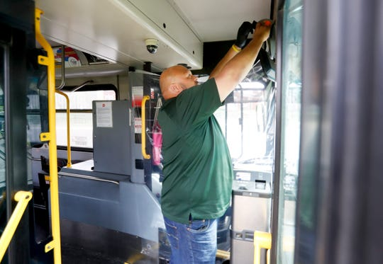 TARC drivers union president Theo Hamilton hangs a shower curtain to provide some separation between the drivers and the passengers on April 7, 2020.