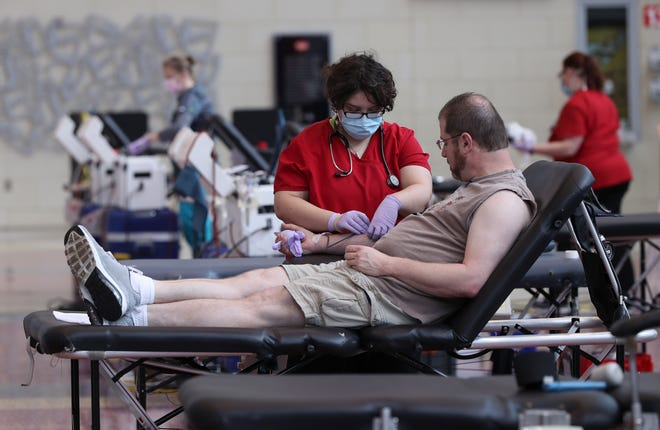 Collection specialist Evan Hernandez checks the progress as Paul Doyle donates blood during the American Red Cross Blood Drive at the Yum Center in Louisville on Wednesday. The Red Cross wants to ensure that there is a stable supply of blood throughout the coronavirus pandemic. April 8, 2020