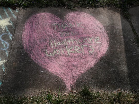 "Neighbors wrote chalk art outside the Crescent Hill home of Dr. Zach Armstrong this week. It says, ""Thank You Healthcare Workers."""