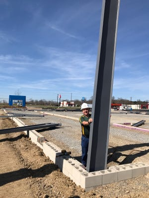 On Monday, Brett Schluter, the owner of Rocket Chevrolet in Shelby, stands beside the first steel post of the new building being constructed after a tornado heavily damaged the dealership on April 14, 2019.