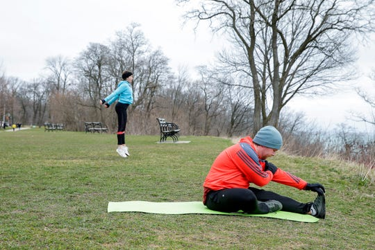 """Tiffany Ervin, left, and her boyfriend, Garrett Simpson, work out together Saturday at Lake Park in Milwaukee.  """"Most of the times we're just staying at home, FaceTiming our friends, reading books and kind of doing puzzles,"""" said Ervin."""