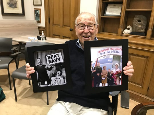 Jim Lovell holds two framed Milwaukee Journal photos from his 1965 return to his hometown with his family after flying in Gemini 7.