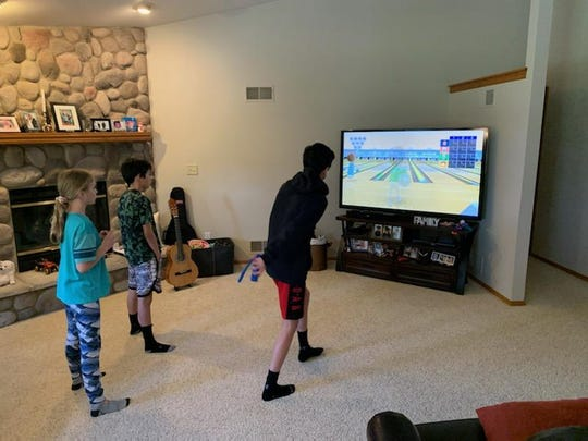 Sussex siblings Matthew Duehing, left, Jacob, right, and Kaitlyn, back, are playing Wii bowling. Their father, Mike, started a Wii bowling league for families to remotely compete with each other during the coronavirus pandemic.