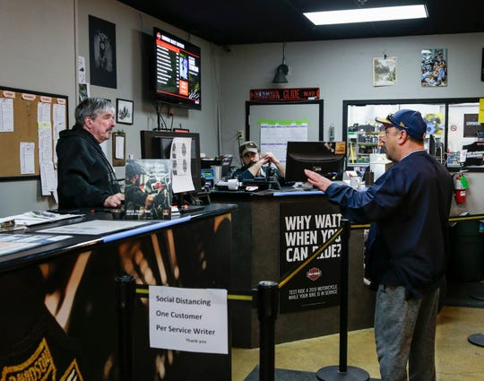 From left, service operations Pat Karl (cq), service consultant Ric Bourbonais (cq) answer customer Dennis Boutris's question at the service department on Wednesday, April 8, 2020 in the Suburban Harley-Davidson, Thiensville, Wisconsin. Zhihan Huang/Milwaukee Journal Sentinel