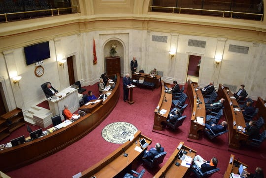 Gov. Asa Hutchinson (at podium) gives his State of the State address from the floor of the Arkansas Senate on Wednesday in Little Rock. Senators kept their space from one another and some sat up in the gallery to maintain proper social distancing.