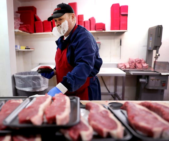 Charles Oxendine works to keep the meat case well stocked at JR's Foodland, in Murfreesboro, Tenn. on Wednesday April 8, 2020.