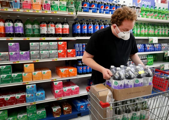 Bryan Cooper stocks shelves at JR's Foodland, in Murfreesboro, Tenn. on Wednesday April 8, 2020.