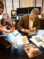 Gov. Bill Lee is handed photos to sign at the Capitol in Nashville on April 6, 2020.
