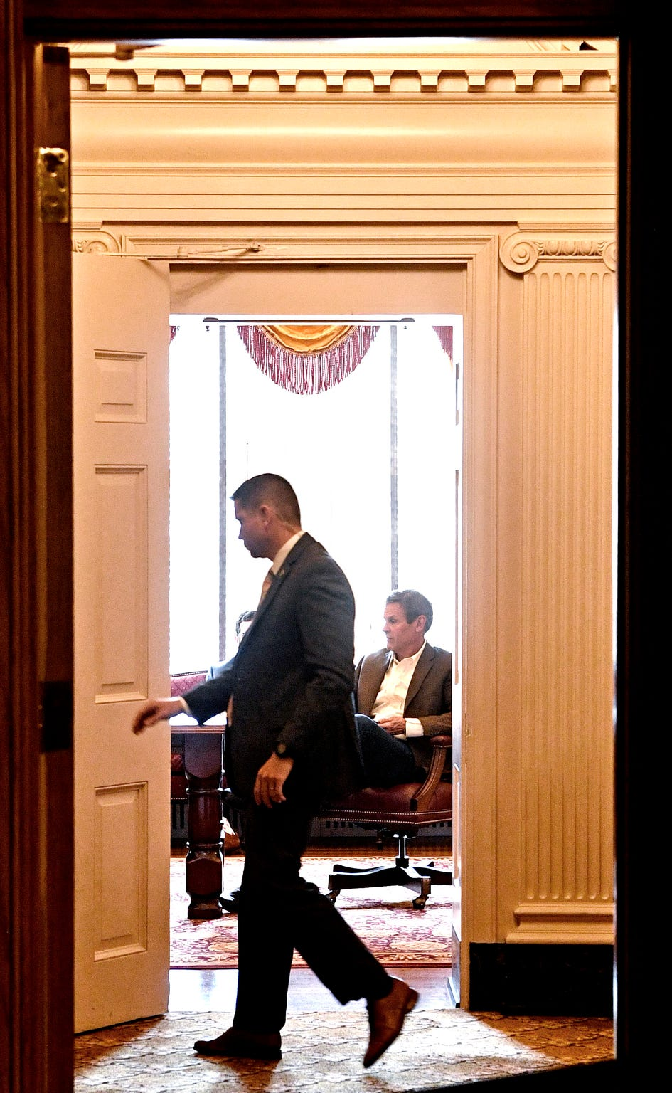 Security personnel close an open door to Gov. Bill Lee's conference room where he attends a meeting with senior staff at the Capitol in Nashville, Tenn. Monday, April 6, 2020.