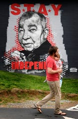 Daniel Schlabach and his daughter Cora take their daily walk past a mural of John Prine at Grimey's in Nashville on Wednesday, April 8, 2020.