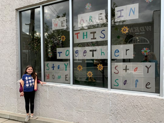 Nevaeh Boehm, 9, outside the Dickson County Help Center building on College Street in front of the sign she created.