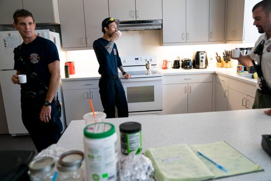 Lt. Daniel Sawyer, left, firefighter and paramedic Arael Contreras, center, and battalion chief Charlie Matthews, right, drink coffee together while they wait for a call at Station 76 on Wednesday, April 8, 2020.