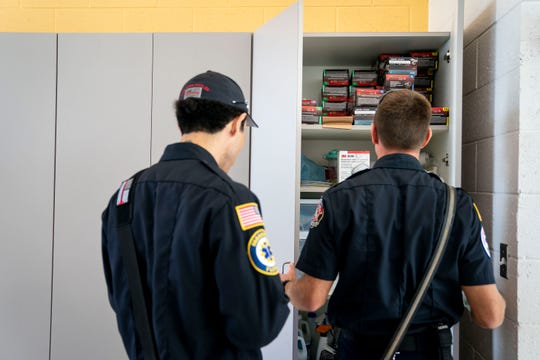 Firefighter and paramedic Arael Contreras, left, and Lt. Daniel Sawyer, right, both with Greater Naples Fire Rescue District, look through a closet containing equipment including disposable gloves and masks at Station 76 on Wednesday, April 8, 2020.